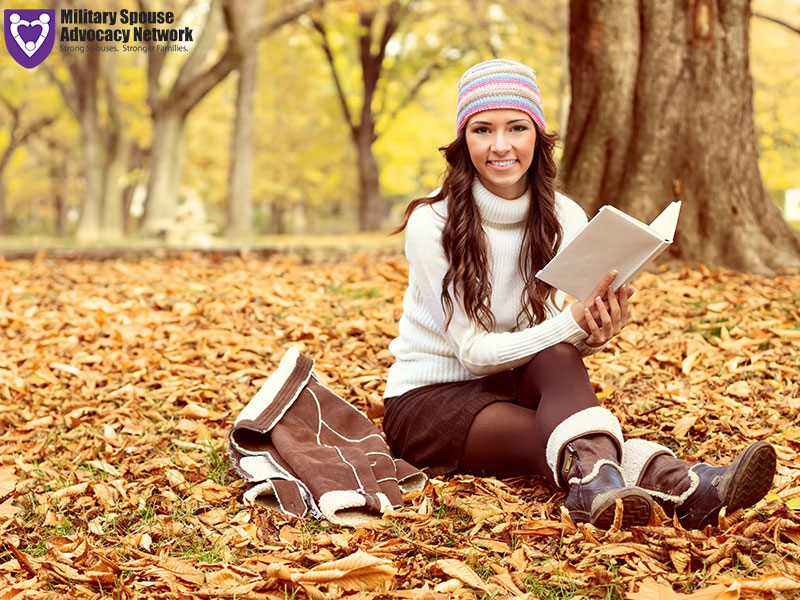 Woman reading book sitting in Fall leaves